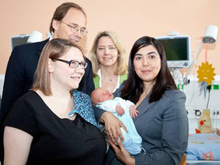 Drei Frauen und ein Mann stehen zusammen mit einem Neugeborenen in einem Krankenhauszimmer.