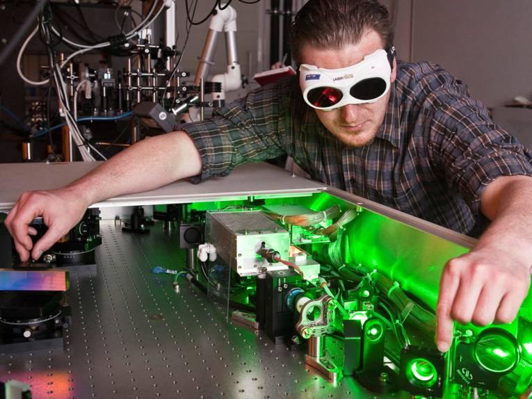 Ein Mann mit Schutzbrille arbeitet an einem grün leuchtenden Gerät.