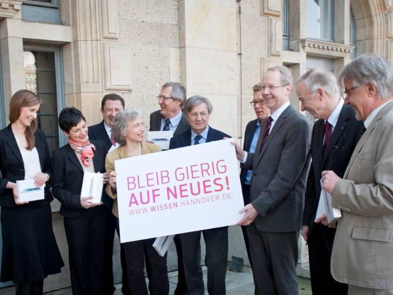 Menschengruppe mit Plakat mit dem Schriftzug: Blieb Gierig, Auf ein Neues. www.wissen.hannover.de