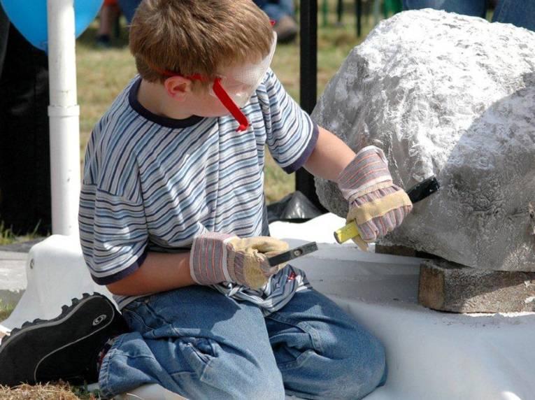 Ein Junge bearbeitet einen Stein.
