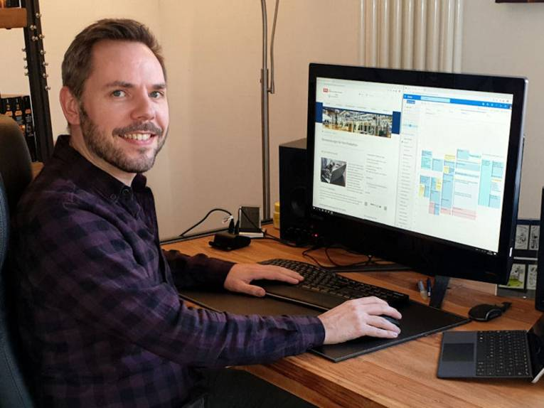 Mann an Schreibtisch mit Bildschirm und Tastatur