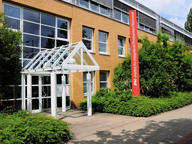 """Eingang eines Gebäudes mit Pylon mit der Aufschrift """"IPH – Institut für Integrierte Produktion Hannover"""""""