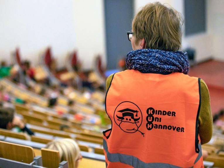 Mensch mit roter Warnweste mit der Aufschrift Kinder Uni Hannover von hinten aufgenommen