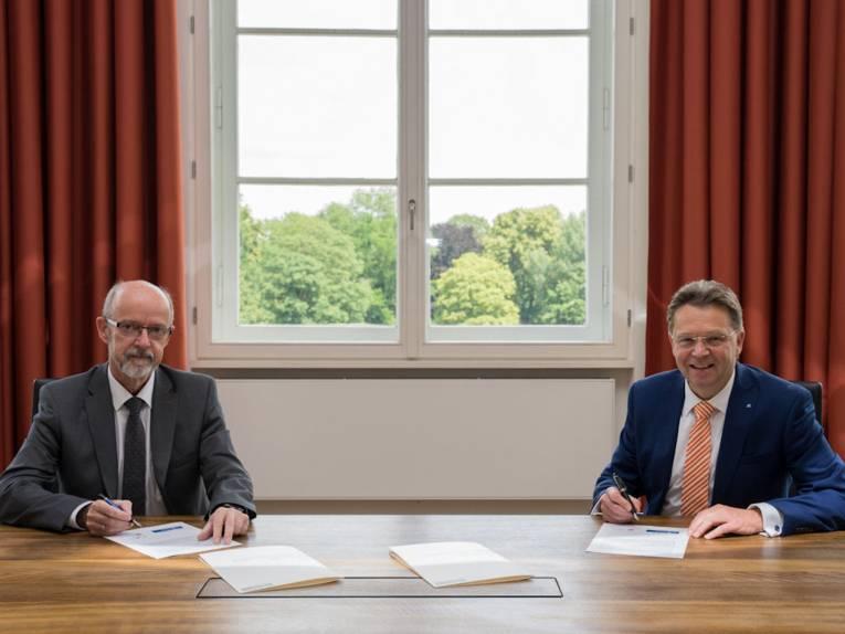Zwei Männer sitzen an einem Schreibtisch