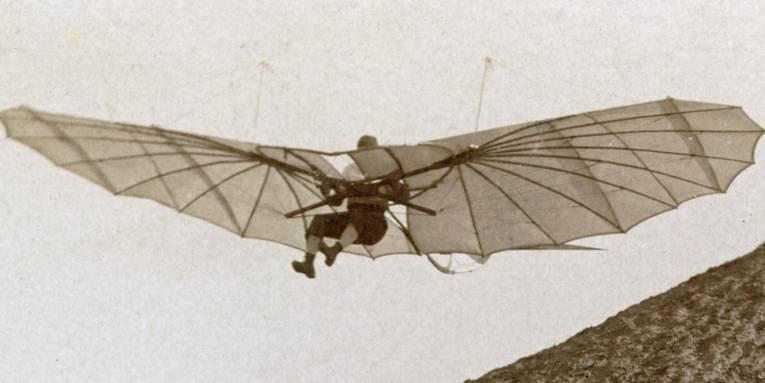 Mensch in Flugapparat, historische schwarz-weiß Aufnahme.