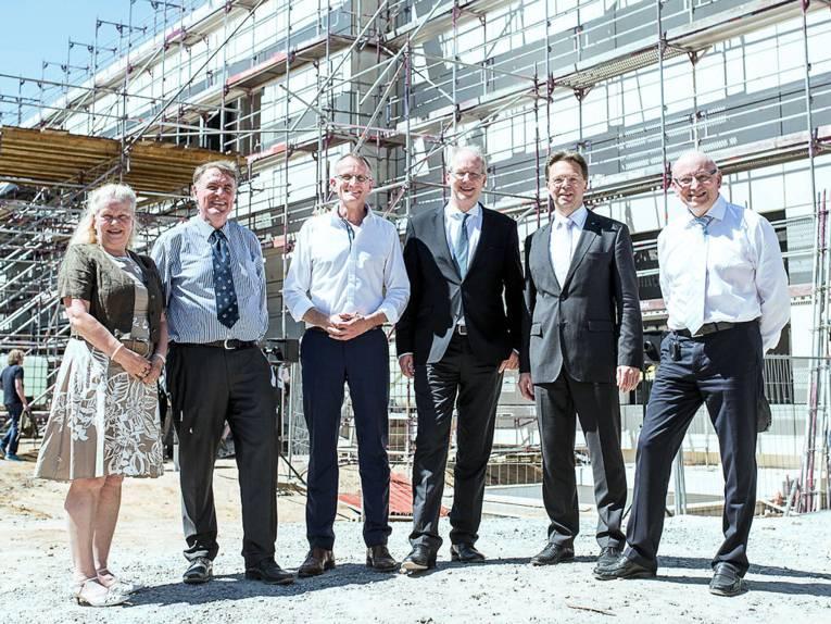 Eine Frau und fünf Männer posieren vor Rohbau eines Gebäudes.