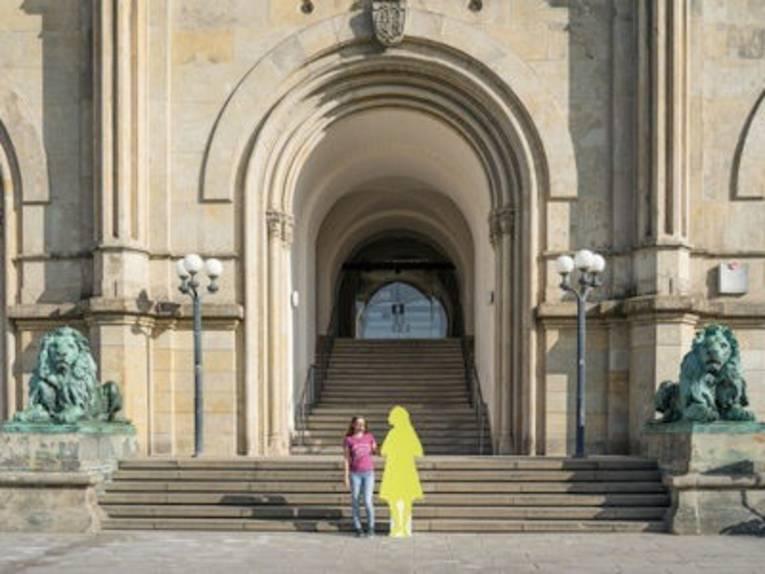 Frau vor Portal eines historischen Gebäudes.
