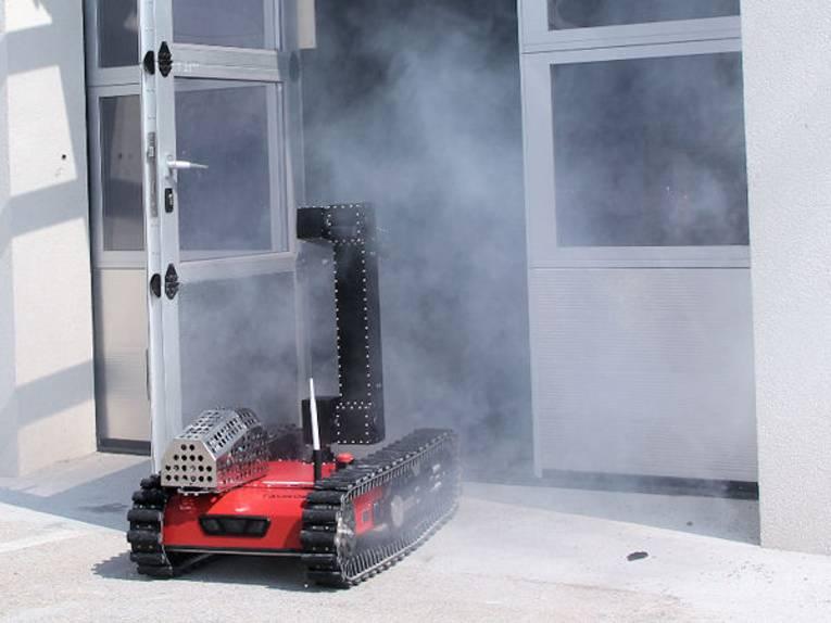 Kleines Kettenfahrzeug fährt aus einer Tür, aus der Rauch kommt.