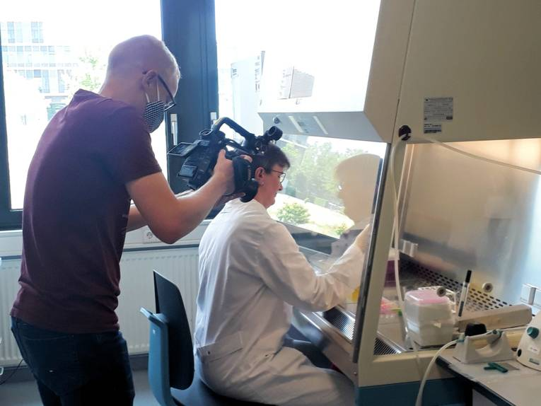 Ein Mann filmt eine Frau in weißem Kittel der Arbeit in einem Labor.