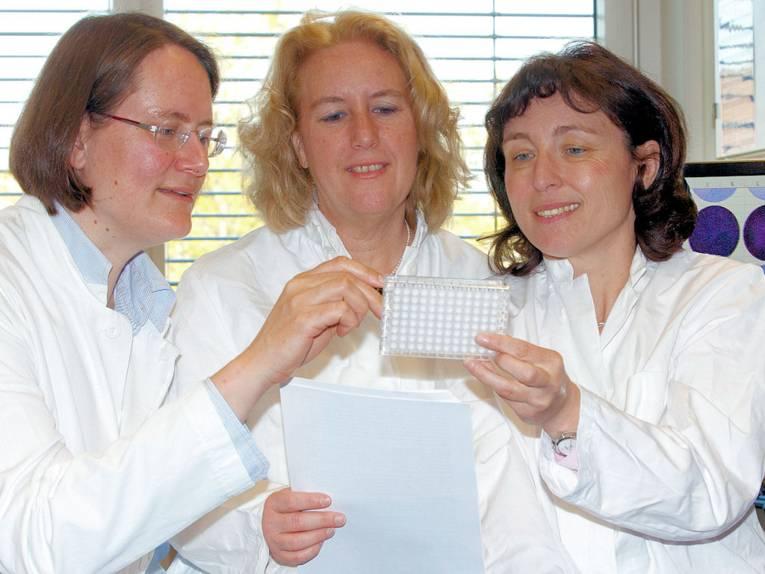 Drei Frauen in weißen Kitteln.