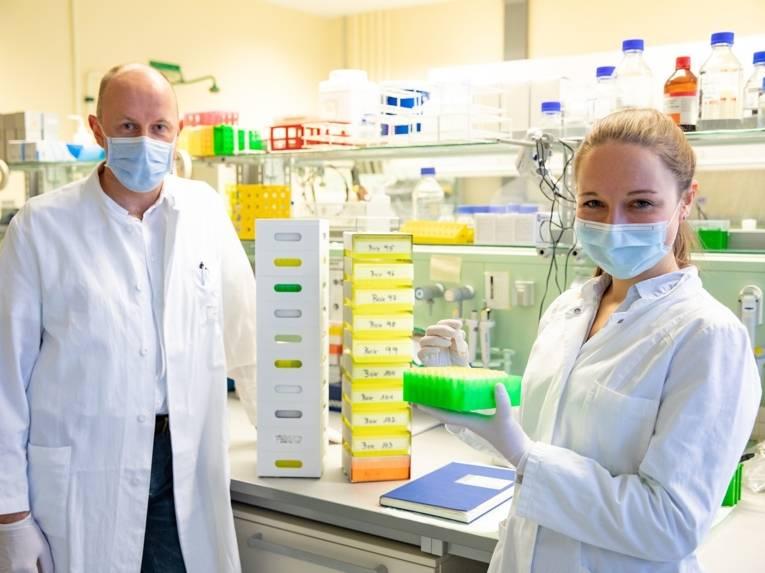 Eine FRau und ein Mann in wießen Kitteln mit Mund-Nasenschutz-Maske in einem Labor.