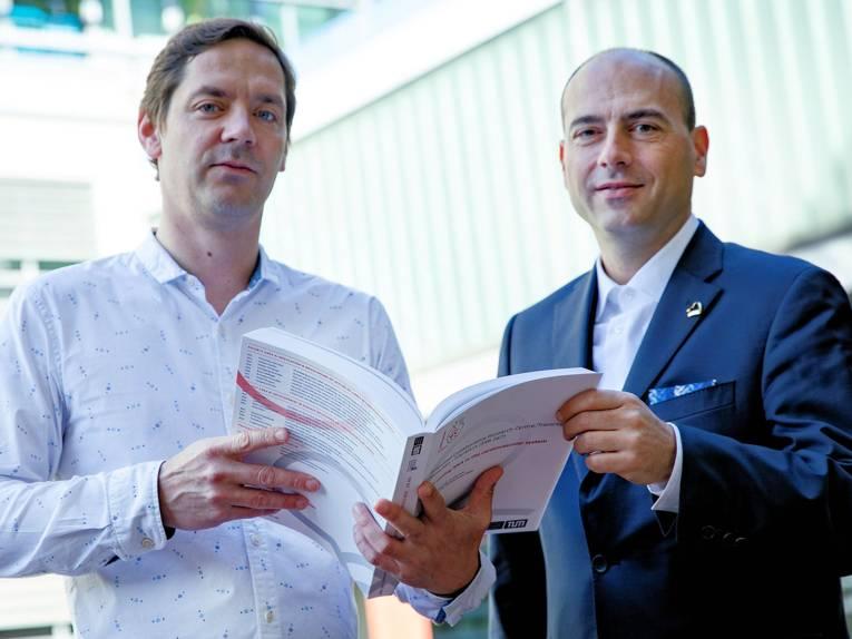 Zwei Männer halten gemeinsam ein aufgeschlagenes Buch