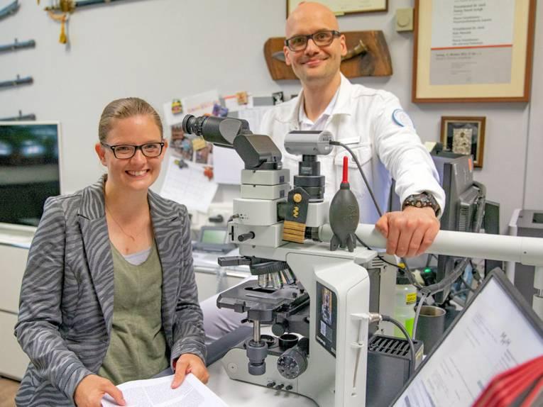 Eine Frau und ein Mann an einem Mikroskop