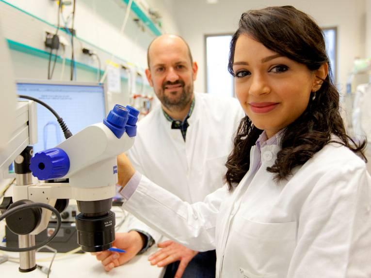 Frau und Mann in weißen Kitteln an Mikroskop.