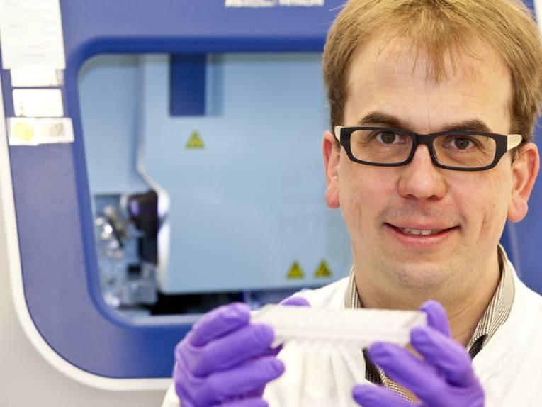 Ein Mann in weißem Kittel hält sich in einer Laborumgebung auf