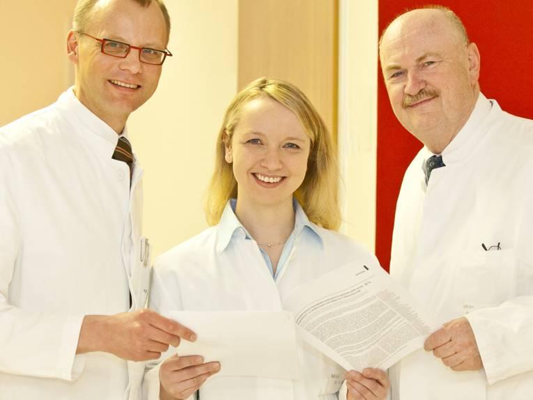 Zwei Männer und eine Frau in weißen Kitteln