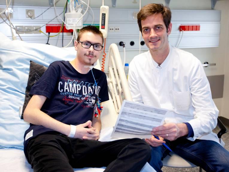 Zwei Männer sitzen auf einem Krankenhausbett.