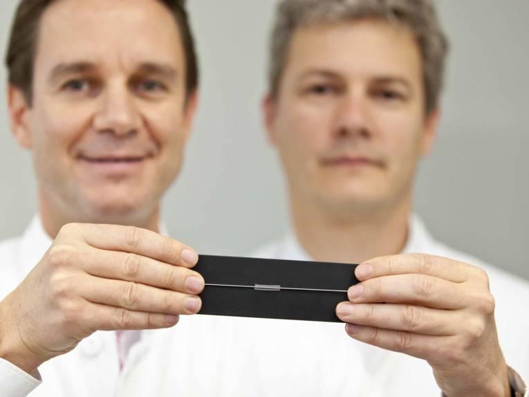 Zwei Männer zeigen eine Art Draht.