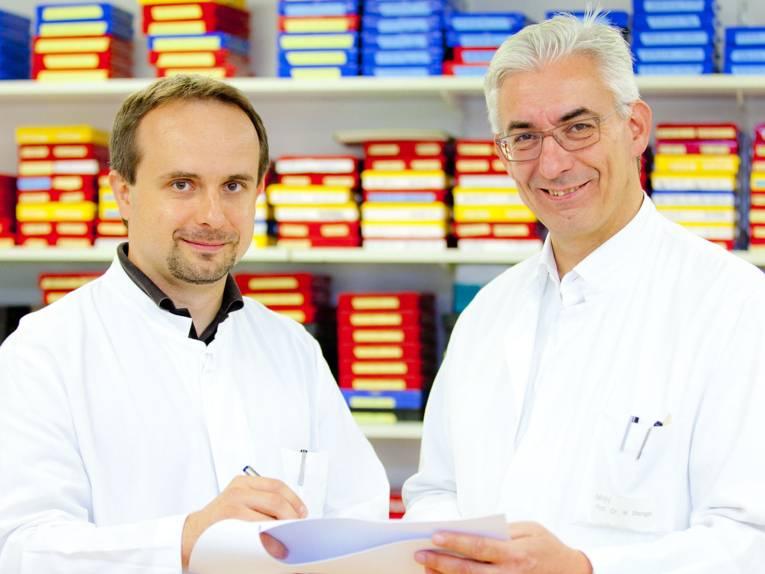 Zwei Männer in weißen Kitteln halten ein Papier und einen Stift in der Hand.