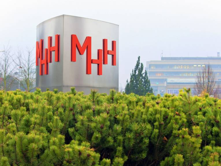 """Eine Säule mit den Buchstaben """"MHH"""", im Hintergrund Gebäude."""