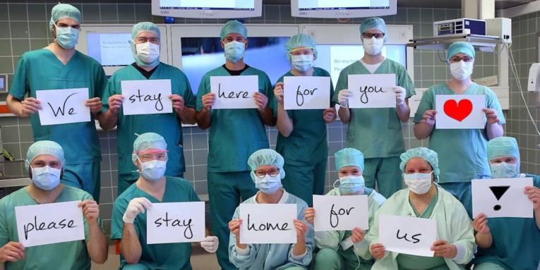 """Medizinisches Personal mit Mundschutz, alle halten Kärtchen hoch deren Aufschriften zusammen den Satz """"We stay here for you, please stay home for us"""" ergeben."""