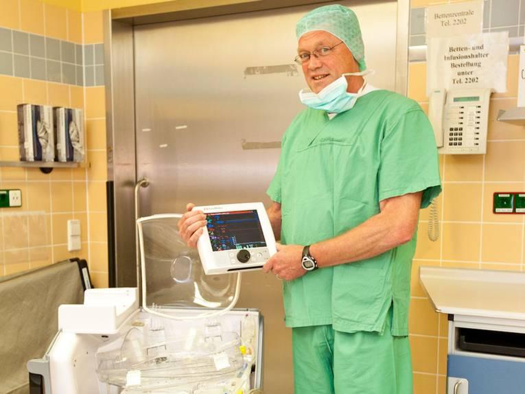 Mediziner mit Kopfhaube und herunterhängendem Mundschutz mit medizinischen Gerät.