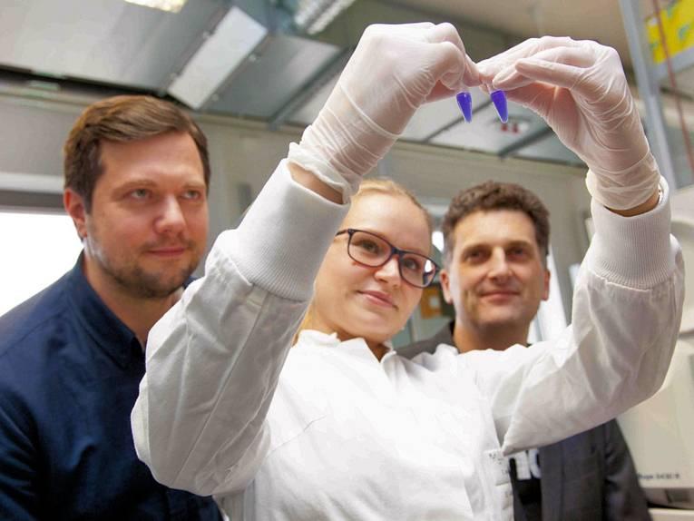 Eine Frau und zwei Männer, die Frau in weißem Kittel mit Handschuhen hält kleine Ampullen hoch.