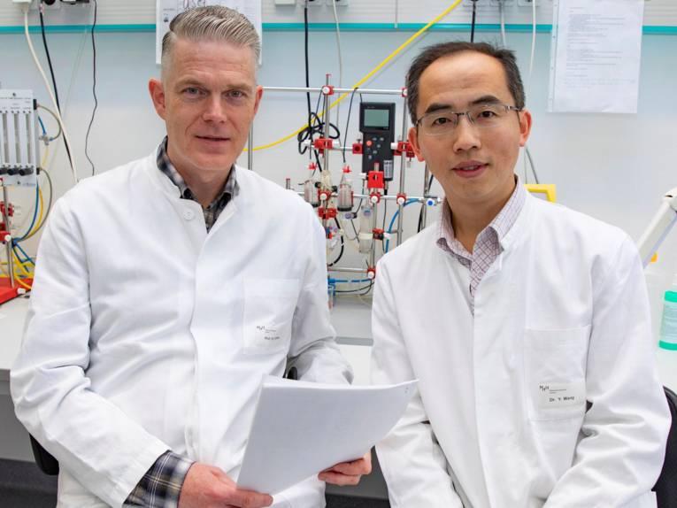 Zwei Männer in weißen Kitteln vor einer Laborapparatur.