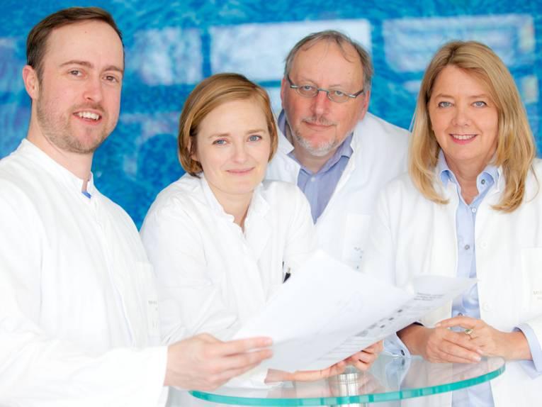 Zwei Frauen und zwei Männer in weißen Kitteln.