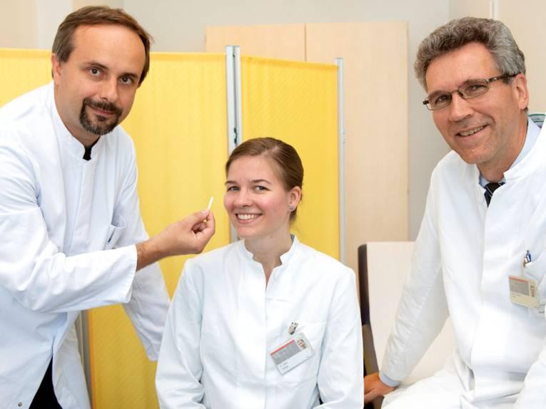 Eine Frau und zwei Männer in weißen Kitteln.