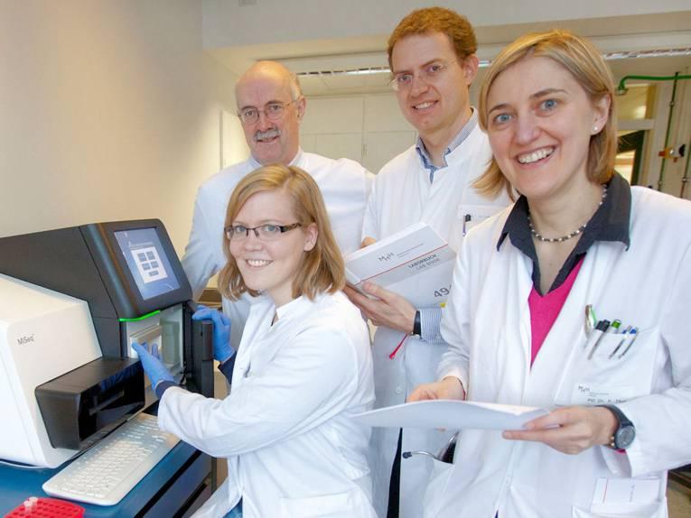 Zwei Frauen und zwei Männer in weißen Kitteln vor einem Gerät mit Bildschirm und Tastatur.