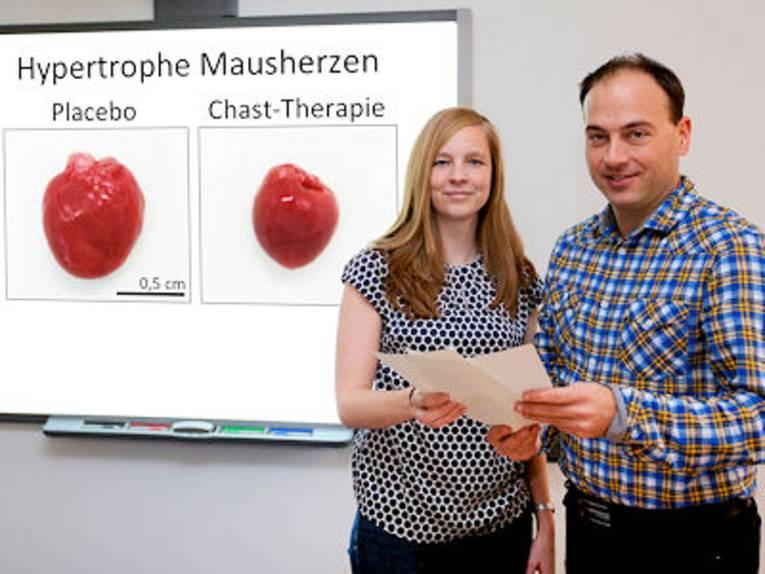 """Eine Frau und ein Mann vor Tafel mit der Aufschrift """"Hypertrophe Mausherzen"""""""