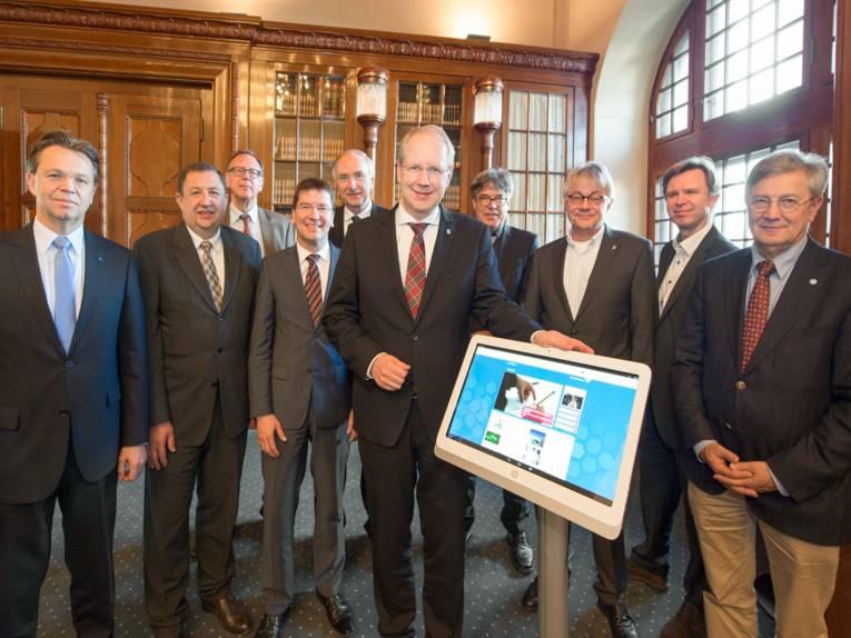 Zehn Männer im Anzug, im Vordergrund ein überdimensional großes Tablet.