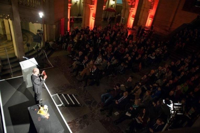 Ein Mann auf einer Bühne, viele Menschen schauen ihm zu