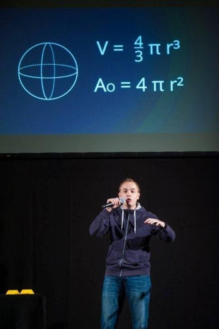 Ein Mann auf einer Bühne, hinter ihm ist eine Leinwand mit Formeln zu sehen.