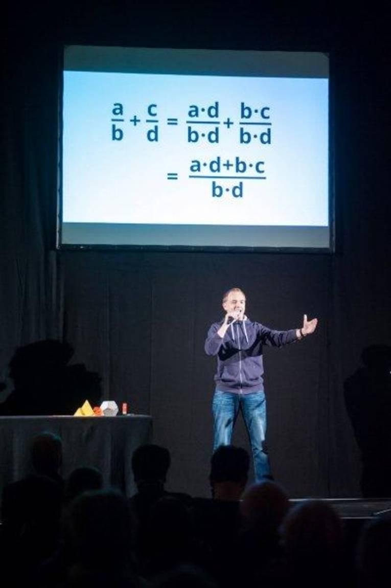 Ein Mann steht auf einer Bühne, hinter ihm ist eine Leinwand mit Formeln zu sehen.