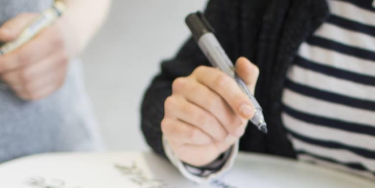 Eine Person hält einen Stift in der Hand