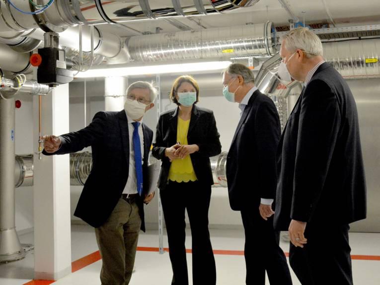 Eine Frau und drei Männer mit Atemschutzmasken