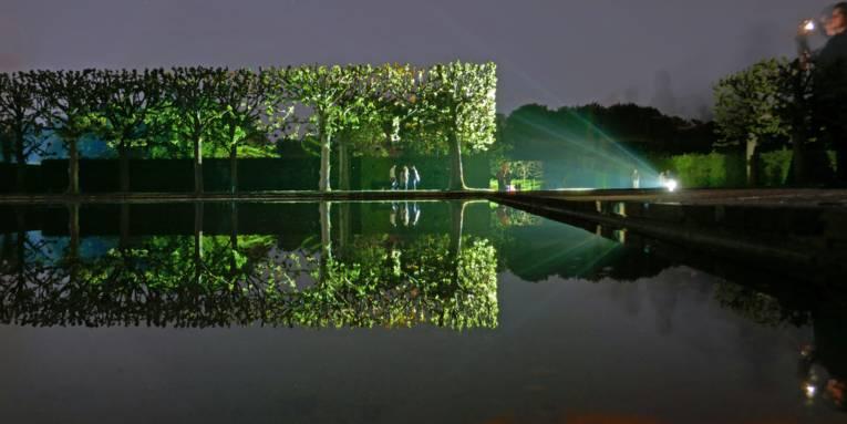 Gartenanlage bei Nacht, die mit Lichtern angestrahlt wird.