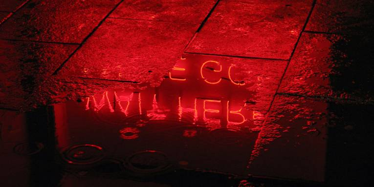 Leuchtbuchstaben werden in einer Wasserpfütze reflektiert