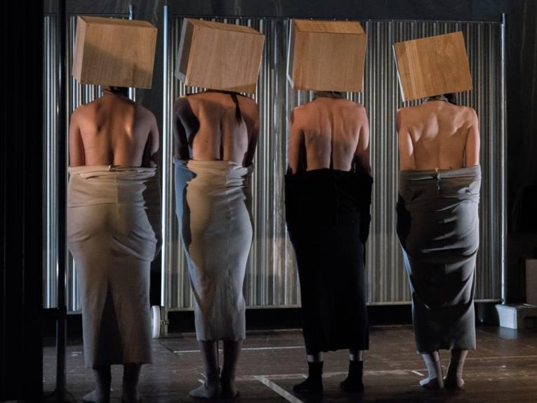 Vier Frauen stehen mit dem Rücken zum Publikum auf einer Bühne und tragen Kartons über ihren Köpfen.