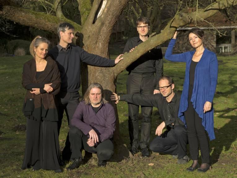 Zwei Frauen und vier Männer stehen vor einem Baum.