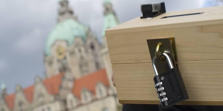 Holzbox mit Zahlenschloss und kleinen elektronischem Gerät