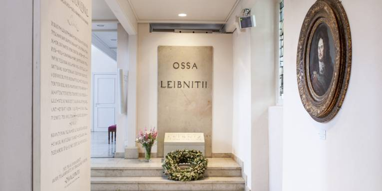 """Grabstätte in einem Raum. An der Wand eine Steinplatte, auf der """"OSSA LEIBNITII"""" steht. Davor liegt auf zwei Treppenstufen ein Kranz, links daneben steht eine Vase mit Blumen. Links hinten ist ein Durchgang erkennbar, links vorne eine weitere, beschriftete Steinplatte an einer Wand. In der rechten Wand ist ein rundes Fenster eingelassen, daneben hängt ein Gemälde."""