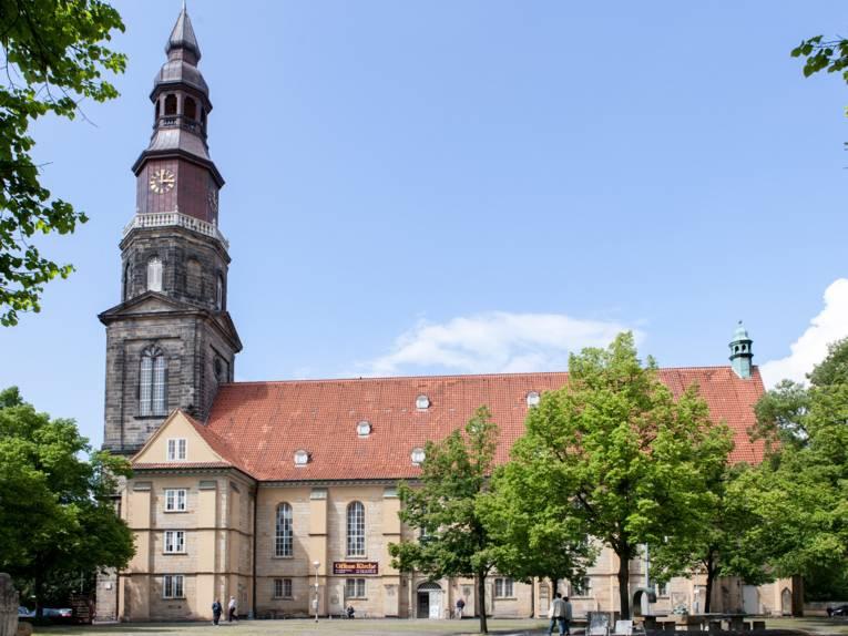 Kirche mit Kirchturm, auf dem Kirchenplatz davor stehen Bäume sowie einzelne Kunstobjekte.