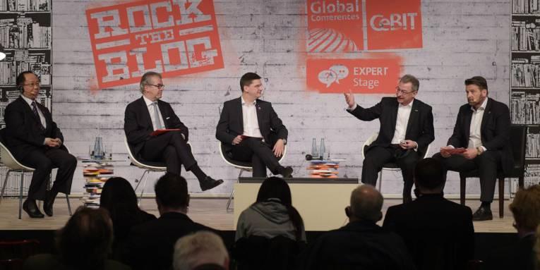 Fünf Männer auf sitzen auf einem Podium.