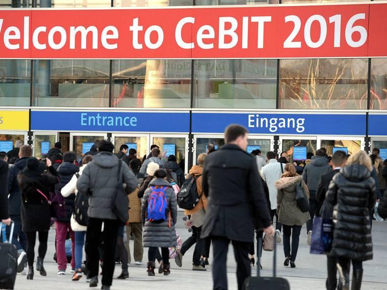"""Menschen gehen auf ein Gebäude mit der Aufschrift """"Welcome to CeBIT 2016"""" zu."""
