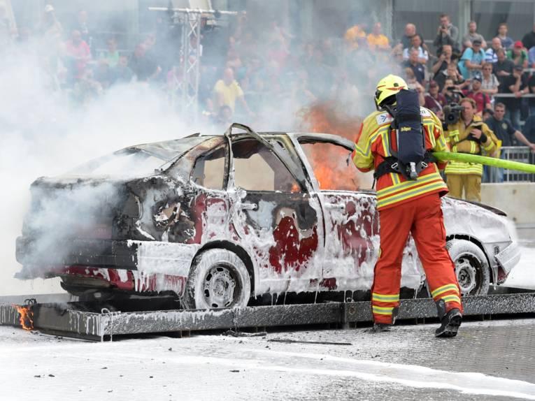 Feuerwehrmann löscht ein brennendes Auto.