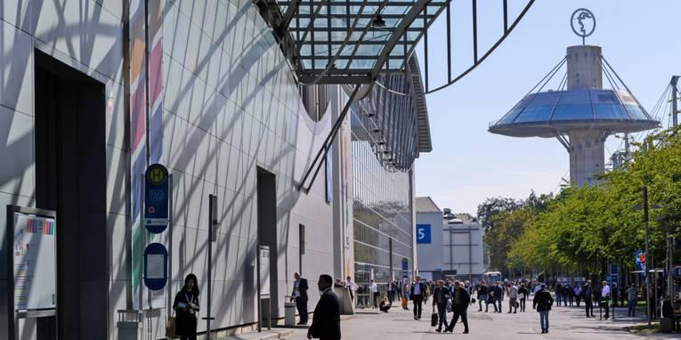 Eingang einer große Halle mit Personen davor, im Hintergrund ein turmartiges Gebäude