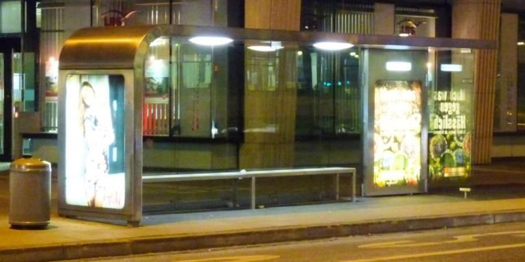 Beleuchtete Bushaltestelle in der Nacht.